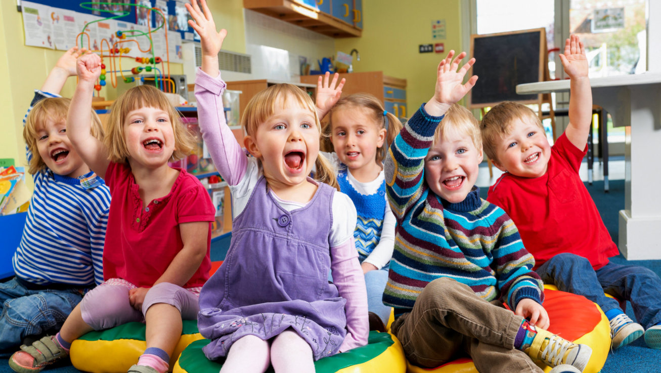 group of toddlers raising their hands